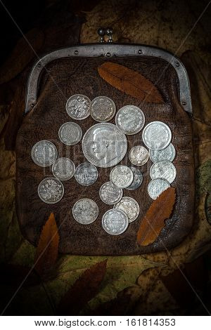 Gloss of old silver coins in a shadow of last times. A purse with silver coins of the Russian Empire the beginnings of the twentieth century.