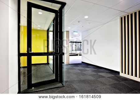 Modern office or apartment area through the hallway with glass doors opened and lights on