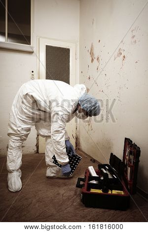 Criminologist technician documenting evidences of blood stains