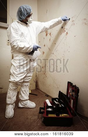 Criminologist technician getting evidences of blood stains