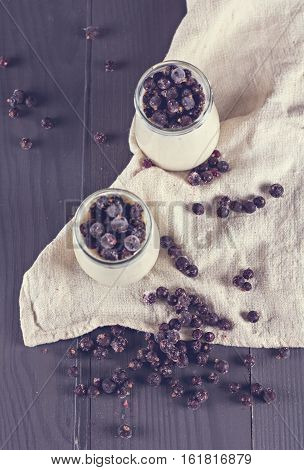 natural yoghurt with a black currant. Glass 0f yogurt with granola and black currants.