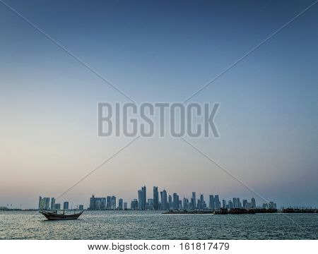 doha city skyscrapers urban skyline view and dhow boat in qatar at sunset