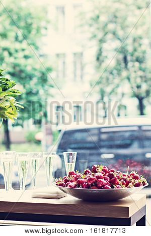 Dish with strawberries and champagne glasses on the table. Dinner party bachelorette party summer party celebration.