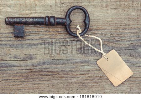 Old rusty key with a paper label lies on a wooden board