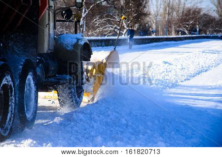 Snow plow truck workiyng in a city park. Kremenchug Ukraine