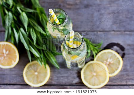 Water bottle with lemon and mint on a wooden table. Infused water with lemon cucumber and mint on wooden background. Mineral water.summer drink.