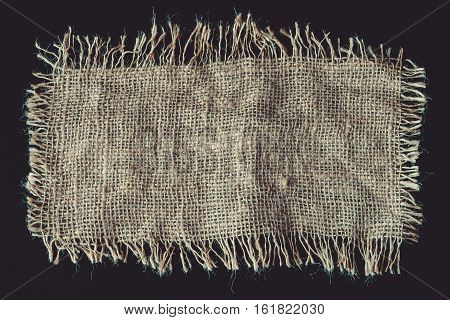 A piece of linen fabric with frayed edges on a black background