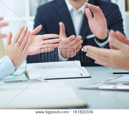 Business partners applauding at the meeting sitting in a row. Successful businesspeople applauding after presentation. Happy group of business team clapping hands in boardroom.