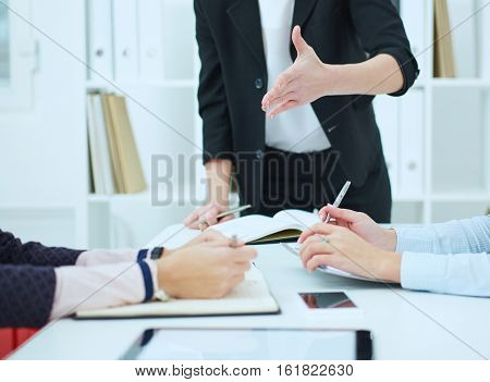 Female boss actively gesticulating during business meeting.