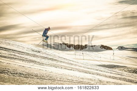 Professional skier performing acrobatic jump on downhill exhibition - Extreme winter sport concept with skiing athlete competing at international race - Dramatic contrasted filter with sunshine halo