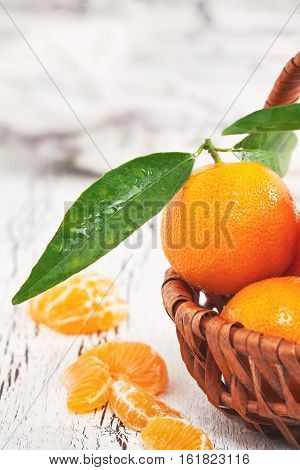 Fresh clementines with leaves in woven basket on white rustic wooden background. Copy space