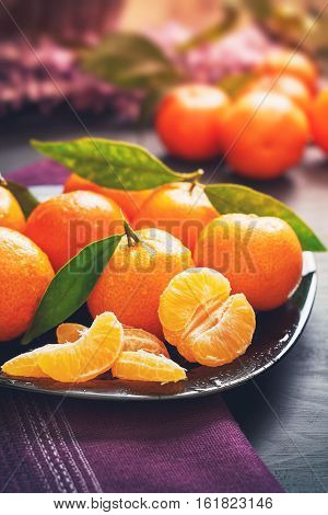 Fresh clementines with leaves served on plate on black wooden table