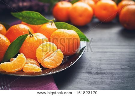 Fresh clementines with leaves served on plate on black wooden table. Copy space