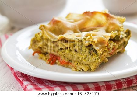 Vegan lasagna with savoy cabbage tofu and red bell pepper served on white plate