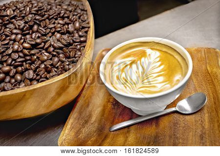 Bowl of coffee beans and an espresso tea with a tree design on a wooden tray with a silver metal spoon close up