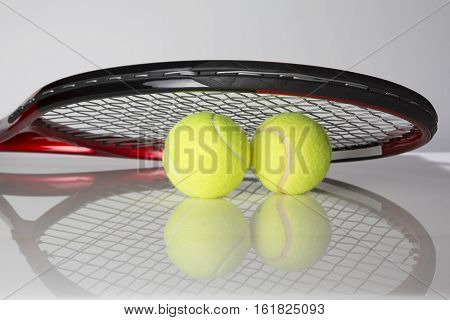Tennis racket and two balls for playing tennis on a gray background
