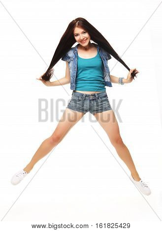 Joyful moments. Full length portrait of a young beautiful girl wearing a  shorts jumping and smiling on white background