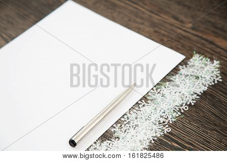 Notebook and pen for writing on the wooden table. Snowflakes