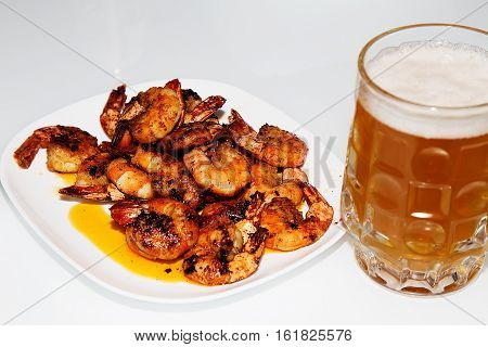 Fried shrimp on a white plate and a glass of beer