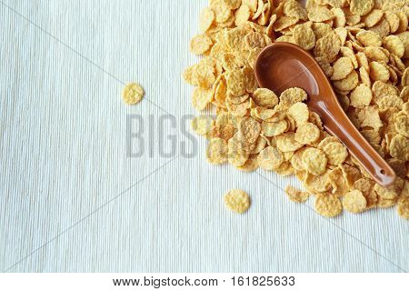 Cornflakes in a spoon on cornflakes background. Close-up.