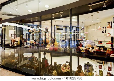 Modern antiques and fancy item shop with various items on the racks beside hanging lights can be seen from the outside wall glass