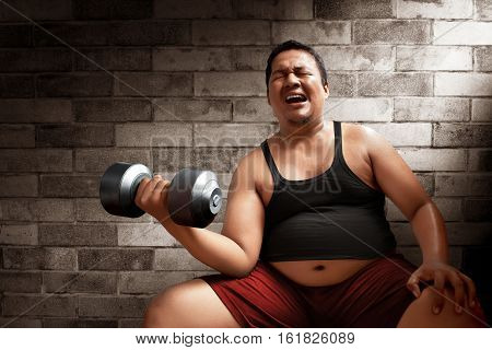 Fat man lifting weights on brick wall background