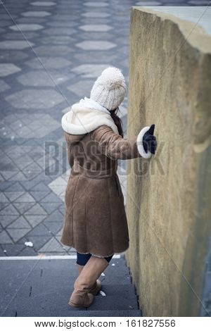 A young woman wearing a winter sheepskin coat is standing on some stairs outside by a rock wall.