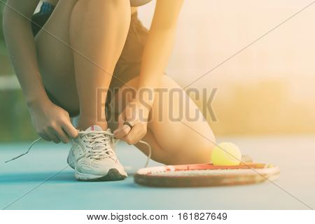 Tennis player tying shoelaces in tennis court at Thailand. tennis racket, tennis ball, tennis ball green color, tennis court, tennis sport