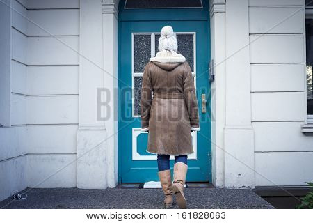 A young woman is willing to go home. On the front door outside a house
