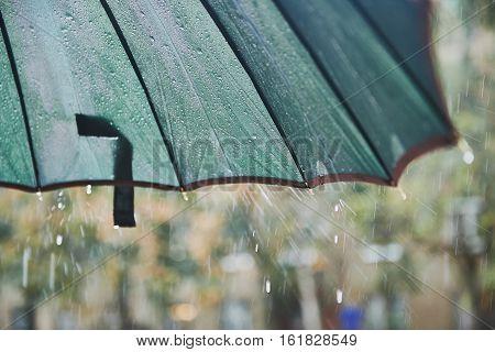 Rain drops falling from the umbrella. Cloudy, damp. Close