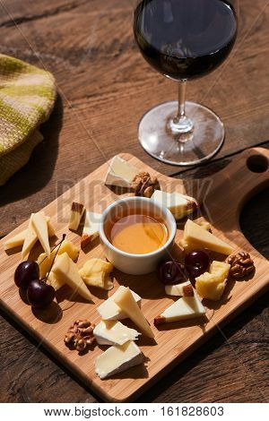 Cheese mix of Parmesan, Mozzarella, Camembert on a wooden Board and a glass of red wine