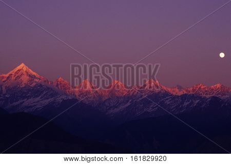 Panchchuli Peaks Munsyari Uttarakhand India: 28July 2005: Pink color Panchchuli Peaks and full moon in the sky view from Munsyari at Uttarakhand India. The Panchchuli peaks are a group of five snow-capped Himalayan peaks lying at the end of the eastern Ku