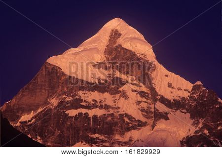 Neelkanth Peak Uttarakhand India-13 December 2006: Golden Neelkanth Peak with dark blue sky at Uttarakhand India. Neelkanth is a mojor peak of the Garhwal division of the Himalayas in Uttarakhand India. substantially lower than the highest peaks of the re