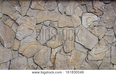 Fragment of decorative brown facing of stone wall