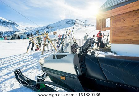 View of winter snow vacation resort - Skisnowboards and snowmobile outside of mountain bar restaurant with back sun light - Holidays and sport concept - Warm vivid filter - Focus on snowmobile