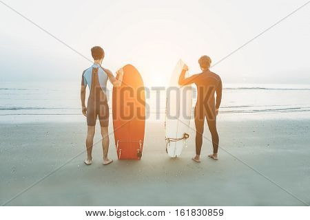 Young surfers waiting the waves on beach with sunlight in background - Sport friends preparing looking the horizon ready for for surfing - Extreme sport and vacation concept - Soft focus on them