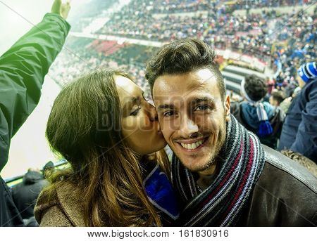Selfie portrait of young couple watching sport soccer match in football italian stadium - Young people having fun together - Love for sport concept - Focus on man - Warm filter