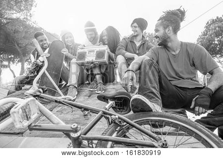 Happy friends listening music in new york skate city park - Breakerskaters and freestyle bikers having fun - Concept of sporty people socializing - Focus on rasta man - Black and white editing