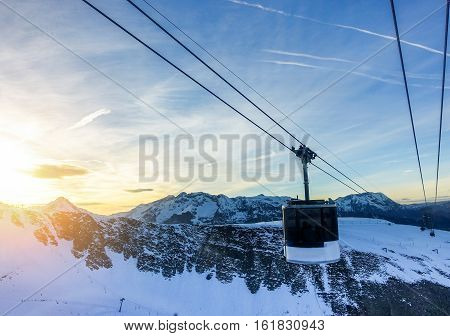 Winter mountains panorama with funicular cable car transporting people on top ski - Landscape ski vacation view with back light at sunset - Holidays and transport concept - Warm filter