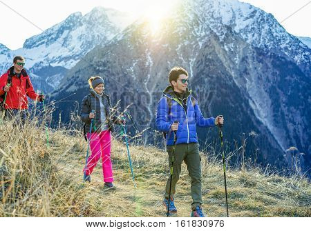 Three trekkers doing excursion on alps top french mountain - Young happy people hiking with back sun light - Sporthealthy lifestyle and recreation concept - Focus on right man - Warm filter