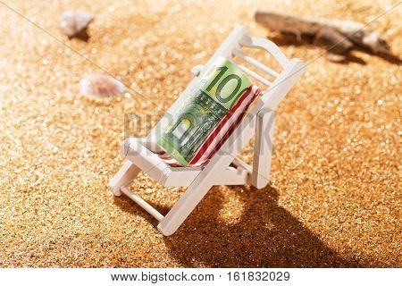 A rolled 100 euro banknote on a deck chair in a beach scene