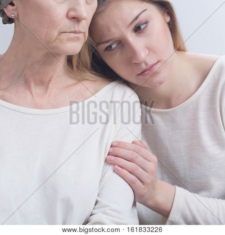 Sad girl embracing serious elderly woman after chemotherapy