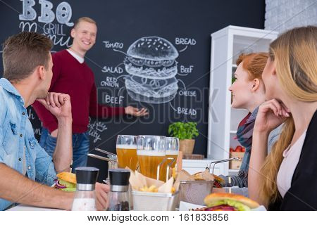 Man Standing Beside Blackboard Menu