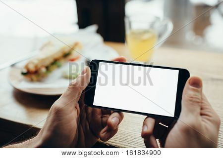 Young Man's Hands Holding Mobile Phone