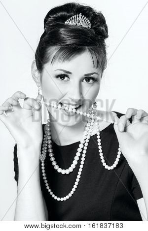 Portrait Of A Beautiful Young Woman Playing With Pearl Beads In Retro Style
