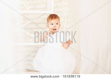 Beautiful Baby Girl In A White Dress In The Interior With Christmas Decorations
