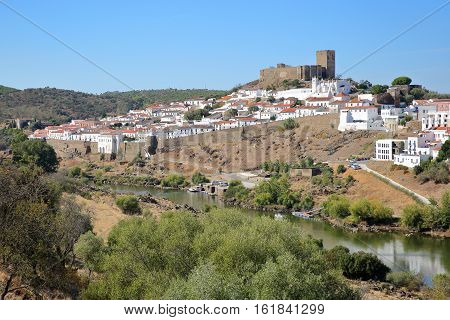 MERTOLA, PORTUGAL: General view of the fortified village from the opposite bank of the river Guadiana