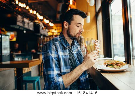Young Man Is Sitting In The Restaurant And Taste A Warm Drink.