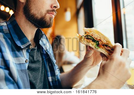 Man In A Restaurant Eating A Hamburger