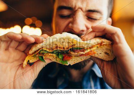 Man In A Restaurant Eating A Hamburger
